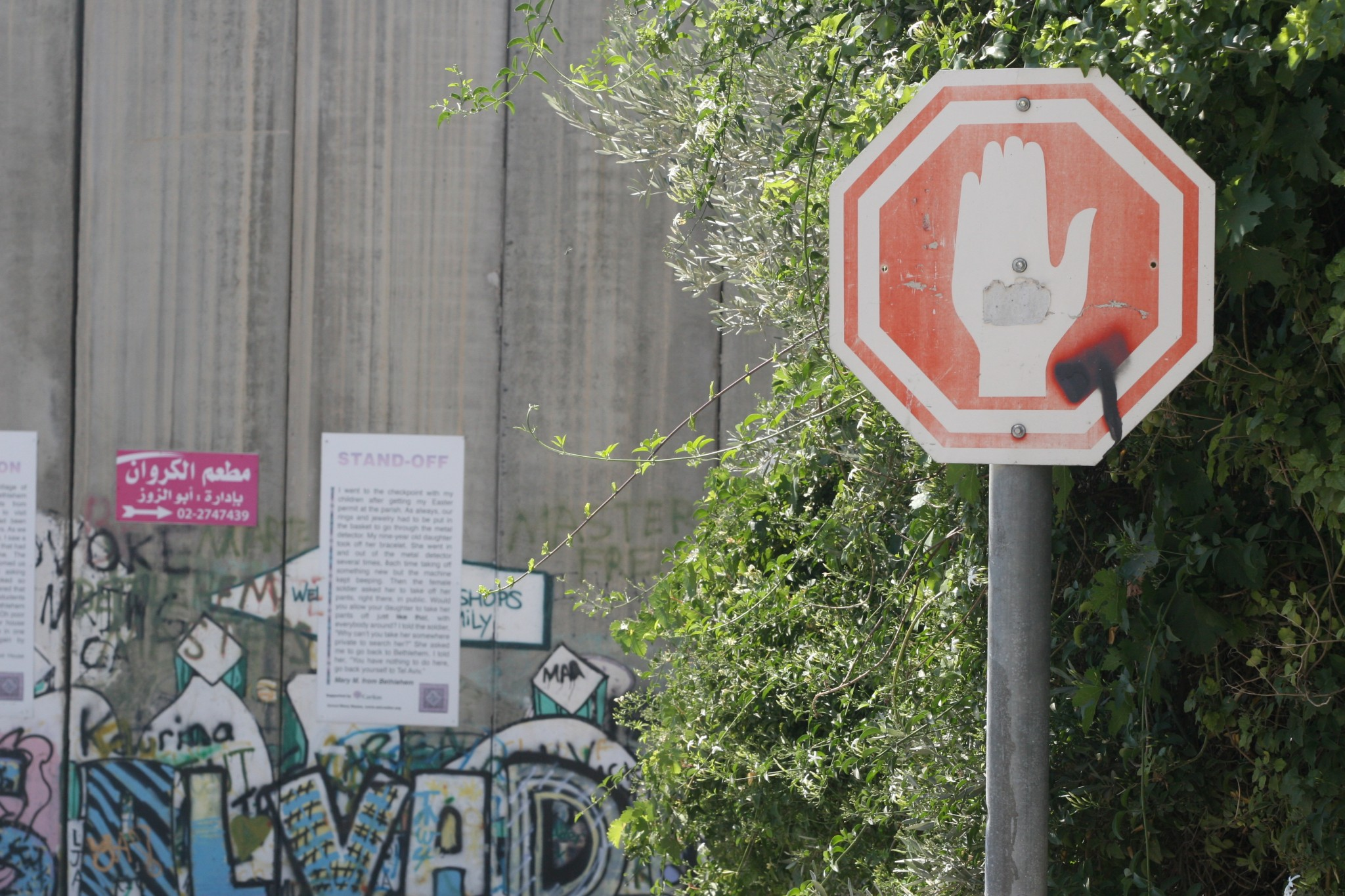 A photo of a street sign in front of the apartheid wall taken in Bethlehem
