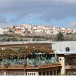 The red sloping roofs and lack of black water tanks identify the hilltop town as an Israeli settlement. It overlooks the Aida Refugee Camp, separated from it by the Wall.